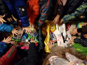 Kindergarten St. Raphael besucht unsere Tafel mit zwei Bollerwagen voller Geschenke